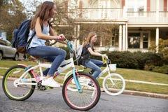 Due ragazze teenager che guidano le bici in via, fine di vista laterale su fotografia stock