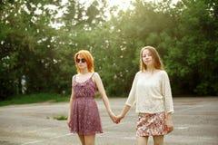 Due ragazze teenager che posano sul campo da giuoco Immagine Stock