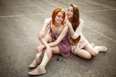 Due ragazze teenager che si siedono sul campo da giuoco Fotografia Stock Libera da Diritti