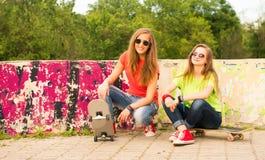 Due ragazze teenager divertendosi insieme al bordo del pattino Outd fotografia stock libera da diritti