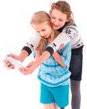 Due ragazze teenager fanno il selfie su un fondo bianco Fotografie Stock