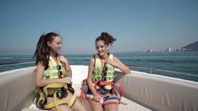 Due ragazze teenager felici che indossano l'aumento delle cinture di sicurezza passano su nell'aria Fotografie Stock Libere da Diritti
