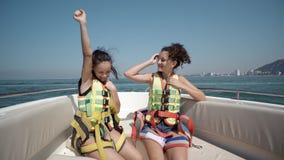 Due ragazze teenager felici che indossano l'aumento delle cinture di sicurezza passano su nell'aria Immagini Stock