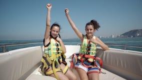 Due ragazze teenager felici che indossano la sicurezza si divertono sul giro con l'yacht di lusso Immagini Stock