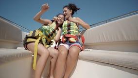 Due ragazze teenager felici che indossano le cinture di sicurezza che ballano su un yacht Immagine Stock Libera da Diritti
