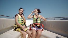 Due ragazze teenager felici che indossano le cinture di sicurezza divertendosi sulla barca Fotografia Stock Libera da Diritti