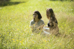 Due ragazze teenager sveglie si siedono sul campo nell'erba nave Fotografie Stock Libere da Diritti