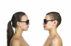 Due ragazze topless che posano su un fondo bianco