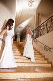 Due ragazze in un vestito da cerimonia nuziale sulle scale Fotografia Stock