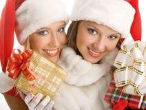 Due ragazze vestite come regali di Santa Claus Happily Hold Boxes With Immagine Stock