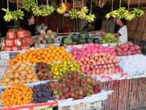 Due ragazze vicino al contatore con i lotti dei frutti tropicali Scatole con l'uva, mandarini, fotografia stock libera da diritti