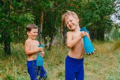 Due ragazzi allegri in pantaloni blu spruzzano l'acqua dagli spruzzatori e dalla risata nella foresta verde immagini stock