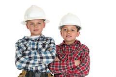 Due ragazzi in armi dei caschi della costruzione piegate Fotografia Stock Libera da Diritti