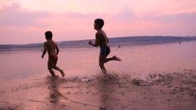 Due ragazzi che corrono insieme sulla spiaggia del ` s del fiume al tramonto archivi video