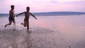 Due ragazzi che corrono sul ` s del fiume tirano contro il tramonto stock footage