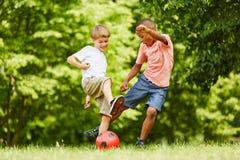 Due ragazzi che giocano a calcio nel parco immagini stock libere da diritti