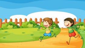Due ragazzi che giocano dentro il recinto di legno Fotografie Stock