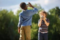 Due ragazzi che giocano il telefono del barattolo di latta fotografie stock