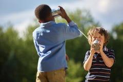 Due ragazzi che giocano il telefono del barattolo di latta immagine stock libera da diritti
