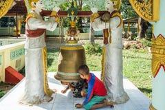 Due ragazzi che giocano sotto la campana dentro un monastero birmano Fotografia Stock