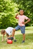 Due ragazzi che tengono i pollici su mentre giocando a calcio immagini stock libere da diritti