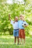 Due ragazzi con calcio come acclamazione degli amici fotografia stock