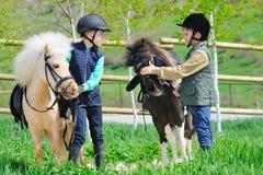 Due ragazzi con i cavallini Immagini Stock Libere da Diritti