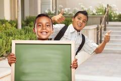 Due ragazzi danno i pollici sulla tenuta del bordo di gesso in bianco sulla città universitaria Immagini Stock