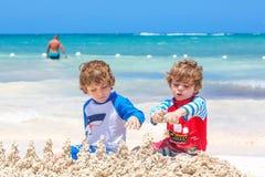 Due ragazzi dei bambini divertendosi con la costruzione del castello della sabbia sulla spiaggia tropicale sull'isola Gioco sano  fotografie stock
