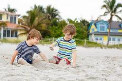 Due ragazzi dei bambini divertendosi sulla spiaggia tropicale, migliori amici felici che giocano, concetto di amicizia Fratelli d fotografie stock libere da diritti