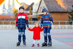 Due ragazzi dei bambini e poca ragazza del bambino che giocano insieme all'aperto il giorno soleggiato Fratelli in vestiti di sic immagine stock