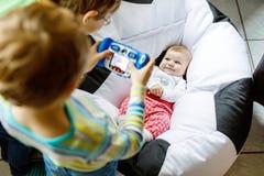 Due ragazzi dei bambini dei fratelli germani che prendono immagine con la macchina fotografica del giocattolo della neonata svegl immagine stock libera da diritti