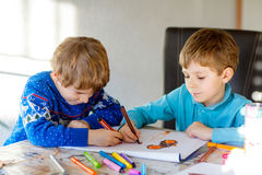 Due ragazzi del bambino alla scuola che dipinge una storia con le penne variopinte Immagine Stock