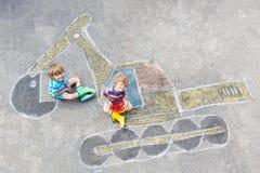 Due ragazzi del bambino con l'immagine del gesso dell'escavatore Fotografia Stock Libera da Diritti