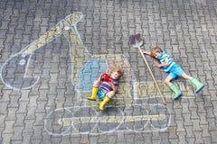 Due ragazzi del bambino con l'immagine del gesso dell'escavatore Immagine Stock