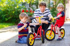 Due ragazzi del bambino e catene felici della riparazione del padre sulle bici e sulla ruota di cambiamento di equilibrio vanno i immagine stock libera da diritti