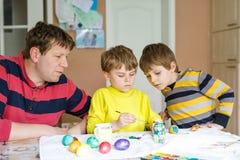 Due ragazzi del bambino ed uova di coloritura del padre per la festa di Pasqua in cucina domestica Fotografia Stock Libera da Diritti