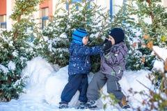Due ragazzi del bambino in vestiti variopinti che giocano all'aperto durante le precipitazioni nevose Svago attivo con i bambini  Fotografie Stock Libere da Diritti