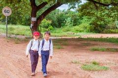 Due ragazzi di scuola che camminano sulla strada della campagna in Cambogia Immagini Stock