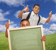 Due ragazzi di scuola che danno i pollici aumentano la lavagna della tenuta Fotografia Stock