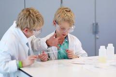 Due ragazzi di scuola durante la classe di chimica Fotografie Stock Libere da Diritti
