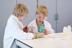 Due ragazzi di scuola durante la classe di chimica Immagini Stock Libere da Diritti