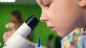 Due ragazzi di scuola molto entusiasti che fanno la scienza sperimentano nel laboratorio della scuola Fine in su stock footage