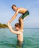Due ragazzi e fratelli colpiscono una posa divertente nell'oceano Immagine Stock Libera da Diritti