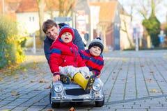 Due ragazzi e padre dei bambini che giocano con l'automobile, all'aperto Fotografia Stock