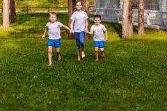 Due ragazzi e una ragazza di dieci anni che corre sull'erba verde Bambini sorridenti felici di estate immagini stock libere da diritti