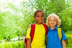 Due ragazzi felici che indossano le borse di scuola stanno insieme immagine stock libera da diritti