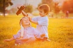 Due ragazzi, giocanti con l'aeroplano sul tramonto nel parco Immagine Stock