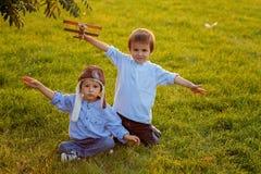 Due ragazzi, giocanti con l'aeroplano sul tramonto nel parco Immagini Stock Libere da Diritti