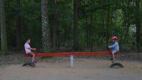 Due ragazzi guidano su un equilibrio dell'oscillazione stock footage